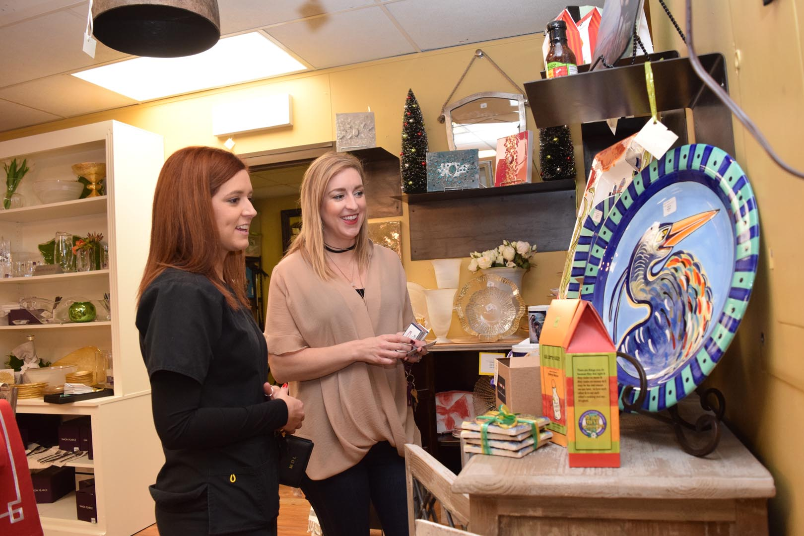 Kristy Lonsberry (right) who works with John Ward Interiors & Gifts located on Metro Drive in Alexandria, helps customer Makayla Liberatore.